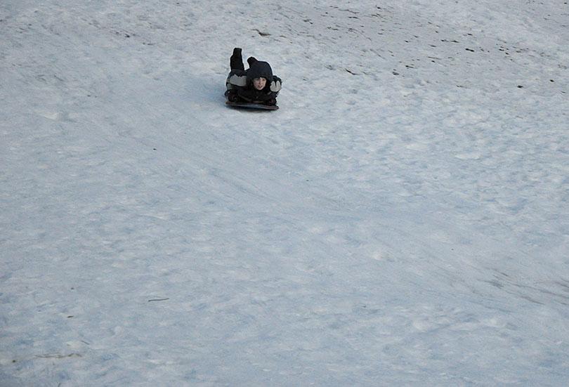 Ethan sledding downhill.